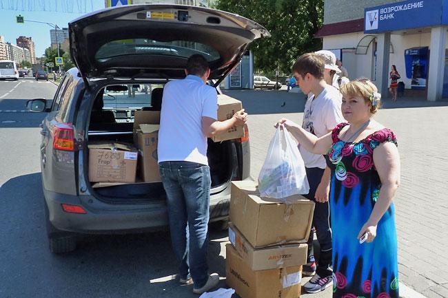 Никита Ширшиков заполняе гуманитарным грузом багажник своей машины